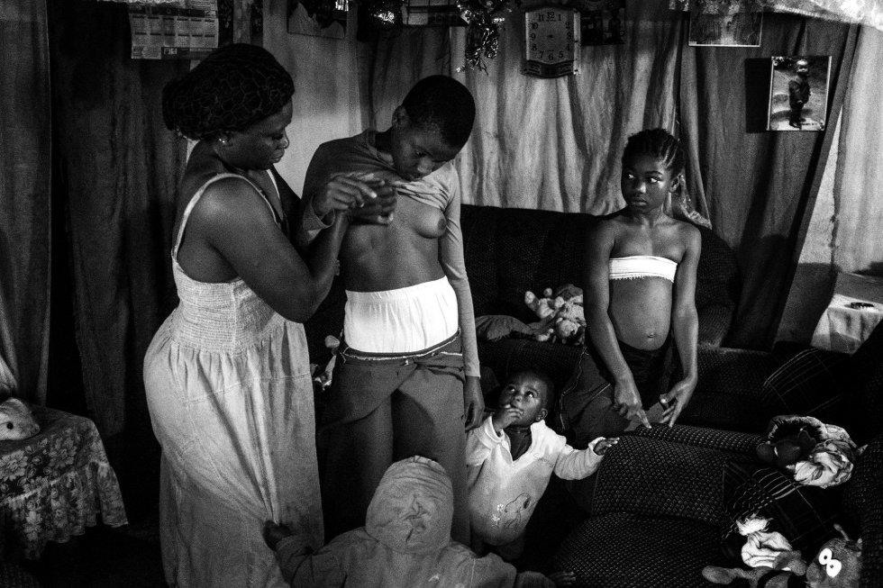 La fotógrafa Heba Khamis ha ganado el primer premio de la categoría 'Contemporary Issues' con esta foto de Veronica, de 28 años, mientras masajea el pecho de su hija de 10 años Michelle, en compañía de sus otras hijas en Bafoussam, Camerún, el 7 de noviembre de 2016.