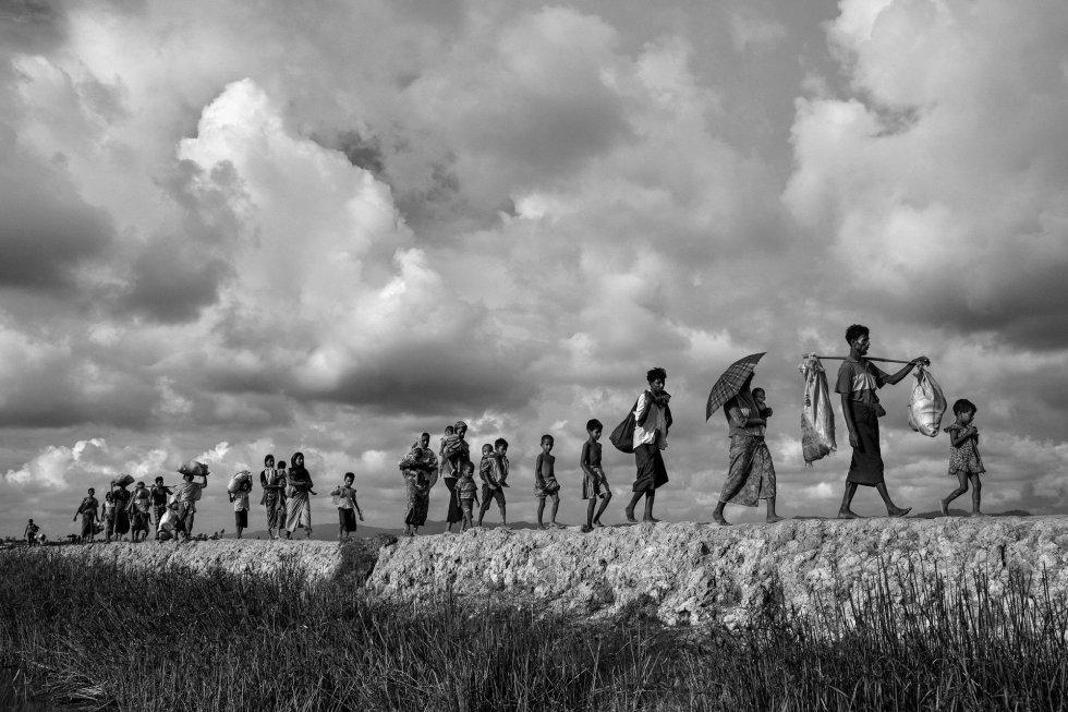 Segundo premio en la categoría de 'General News Stories' hecha por Kevin Frayer. Refigiados rohingyas transportan sus pertenencias huyendo de Myanmar y de camino hacia Bangladesh el 2 de octubre de 2017.