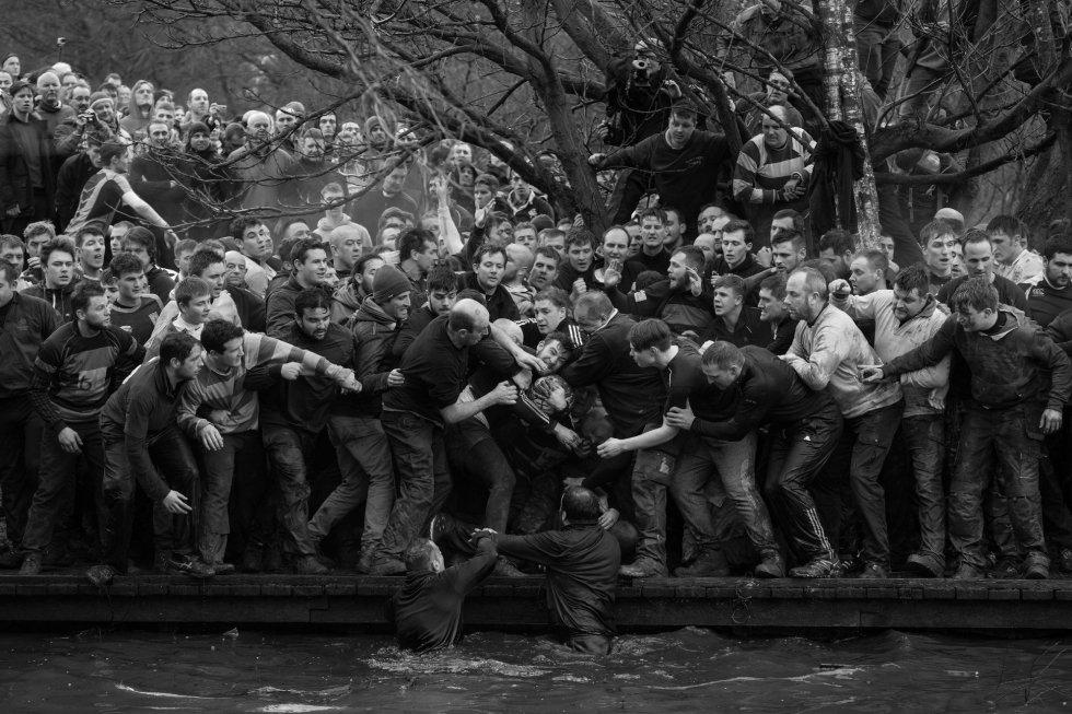 Imagen captada por el fotógrafo Oliver Scarff, ganador del primer premio de la categoría 'Sports - Singles'. La foto muestra a los miembros de equipos contrarios, los Up'ards y Down'ards, luchando por el balón durante el histórico y anual partido de fútbol Royal Shrovetide en Ashbourne, Derbyshire (Reino Unido), el 28 de febrero de 2017.