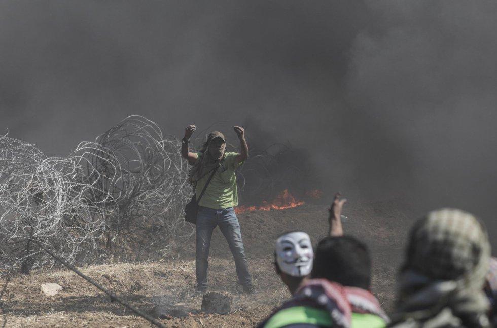 Un manifestante palestino pide ayuda a varios camaradas para que tiren de una alambrada de espinos instalada por las tropas israelíes