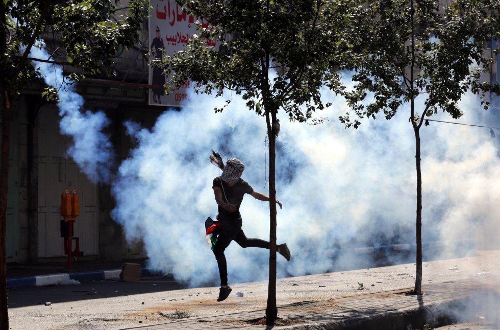 Un palestino aleja un bote de gas lacrimógeno durante un enfrentamiento en la ciudad cisjordana de Hebrón
