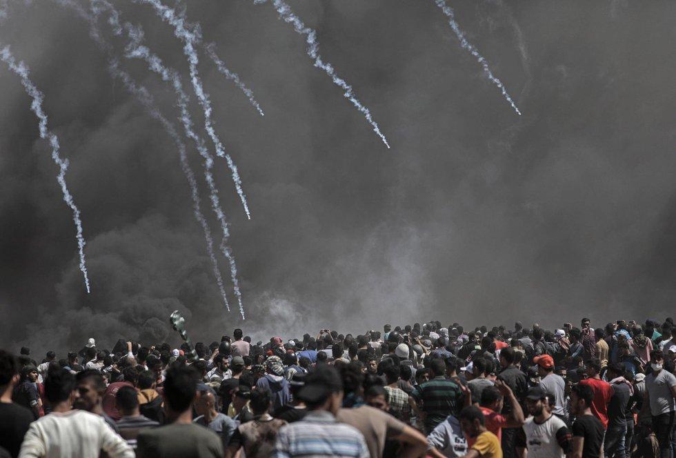 Varios manifestantes palestinos ante un muro de gas lacrimógeno