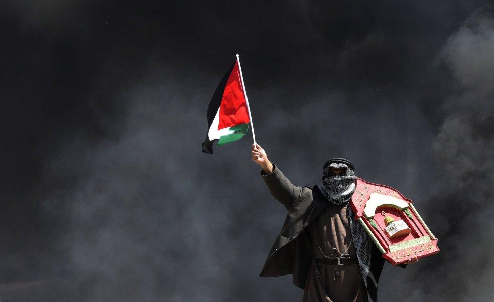 Un manifestante palestino se protege del humo durante unas protestas en la ciudad cisjordana de Ramala