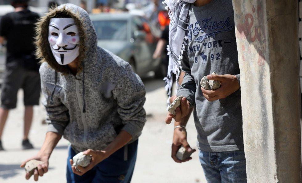 Manifestantes palestinos se ponen a cubierto durante unas protestas en la ciudad cisjordana de Ramala