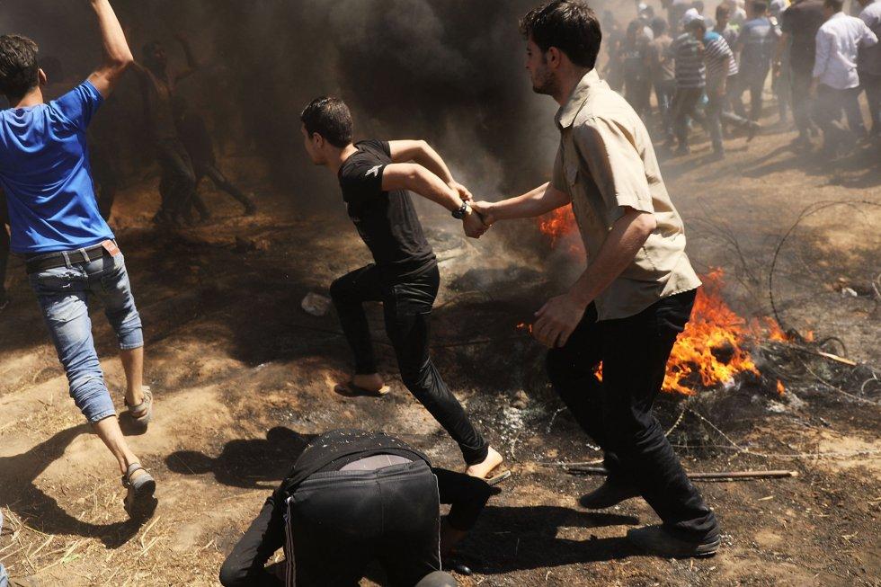 Un grupo de palestinos se apresuran para llegar a la valla fronteriza