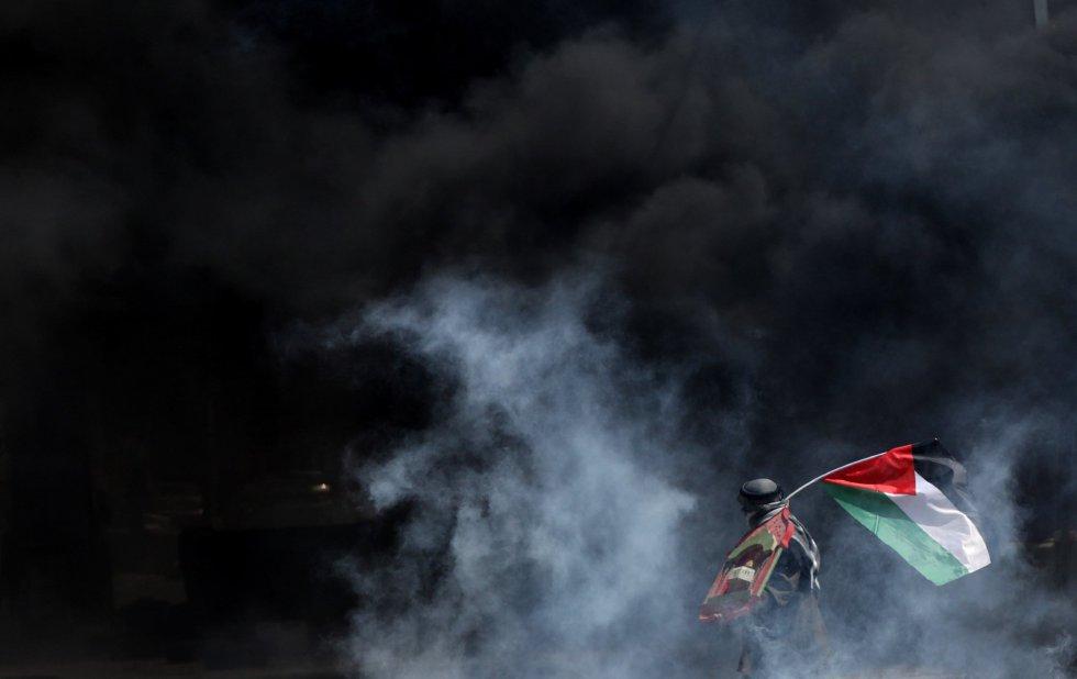 Un manifestante palestino se cubre del gas lacrimógeno