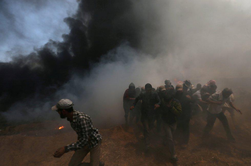 Un grupo de manifestantes palestinos se protegen durante las protestas de este 14 de mayo