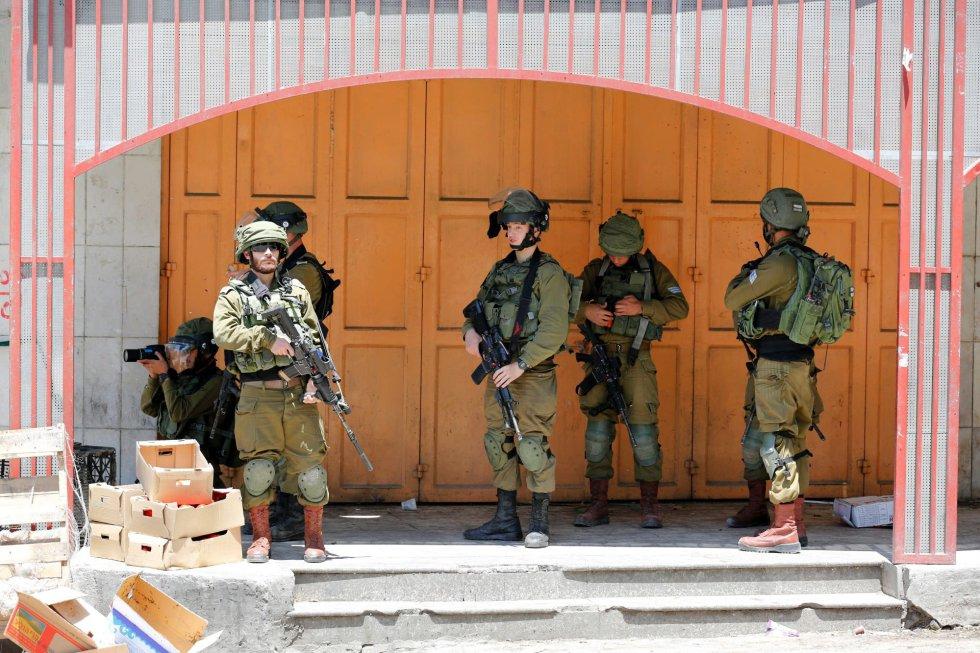 Soldados israelíes toman posiciones durante un enfrentamiento con manifestantes palestinos en la ciudad cisjordana de Hebrón