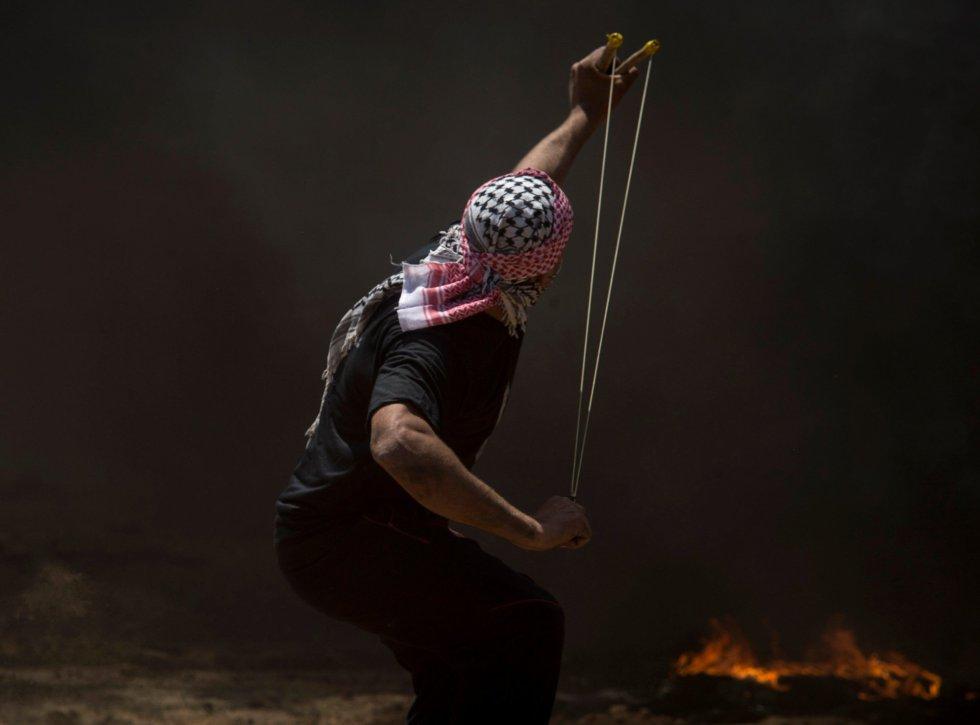 Un manifestante palestino lanza una piedra durante las protestas en la frontera entre Gaza e Israel