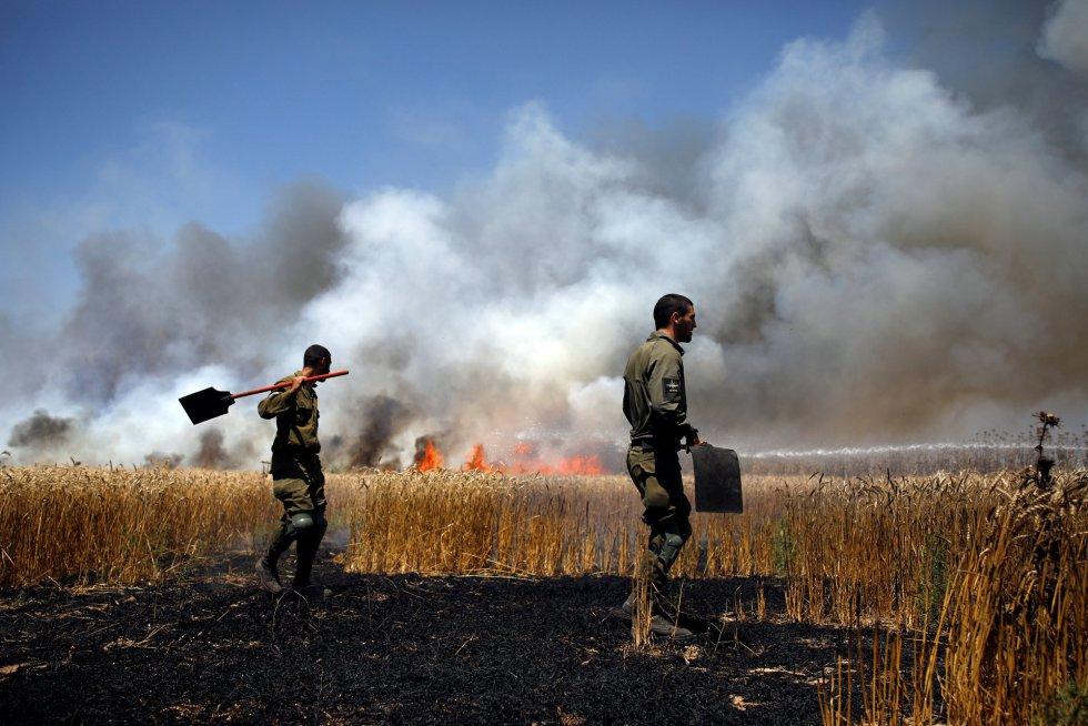 Un soldado israelí intenta sofocar el fuego