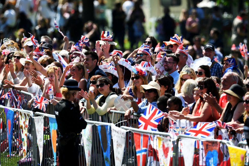 Gente esperando el paseo en carruaje de caballos de los nuevos duques en Windsor, Inglaterra.