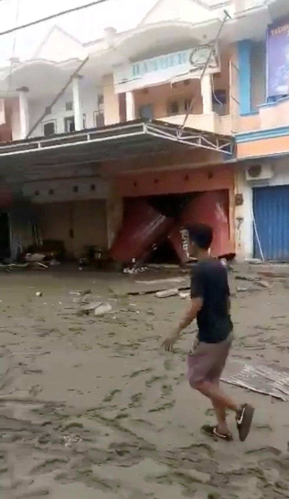 Un joven entre los escombros y ruinas de las casas derrumbadas en Palu.