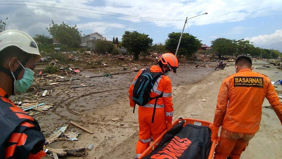 Trabajadores del servicio de emergencia realizando las labores de búsqueda en la playa de Palu.