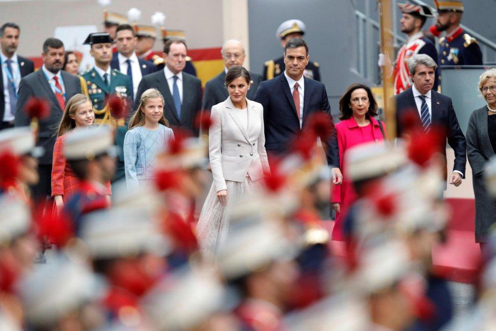 La Reina Letizia, junto a sus hijas, la Princesa Leonor y la infanta Sofía, el presidente del Gobierno, Pedro Sánchez (3d), la ministra de Defensa, Margarita Robles (2d) y el presidente de la Comunidad de Madrid, Angel Garrido (d), al inicio del desfile militar, hoy en Madrid, uno de los actos conmemorativos del Día de la Fiesta Nacional, que presiden los Reyes junto a sus hijas, la princesa Leonor y la infanta Sofía.