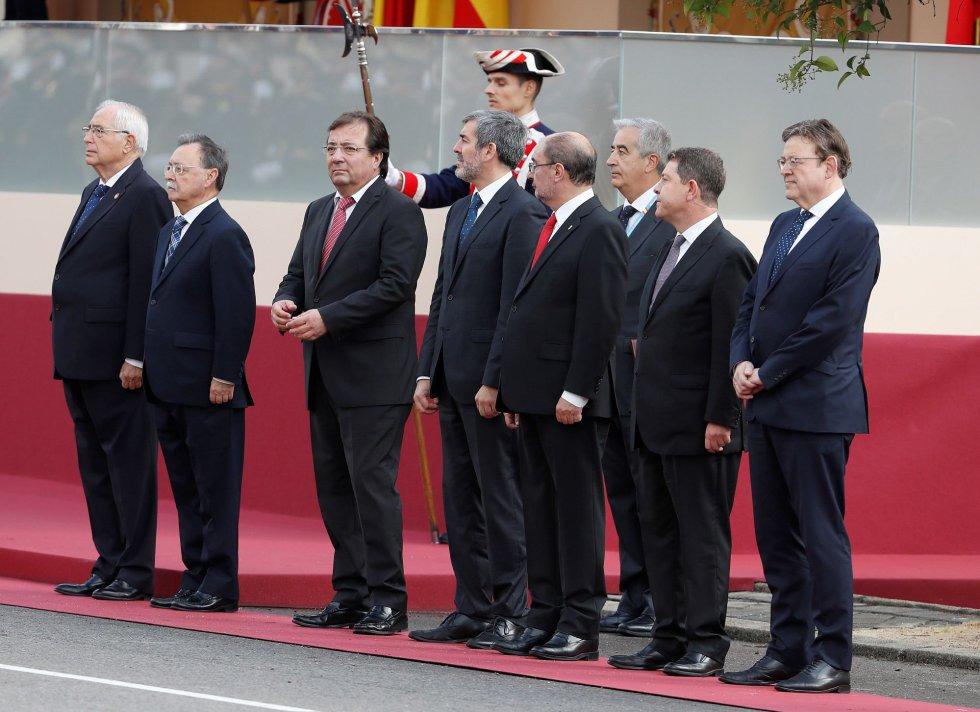 El presidente de Melilla, Juan José Imbroda (i), el presidente de Ceuta, Juan Jesús Vivas (2i9, el presidente de Extremadura, Guillermo Fernández Vara (3i), el presidente de Canarias, Fernando Clavijo (4i), el presidente de Aragón, Javier Lambán (3d), el presidente de Castilla-La Mancha, Emiliano García-Page (2d), y el presidente de la Comunidad Valenciana, Ximo Puig (d), momentos antes del inicio del desfile militar que presiden hoy los Reyes en la plaza de Lima de Madrid con motivo del Día de la Fiesta Nacional.