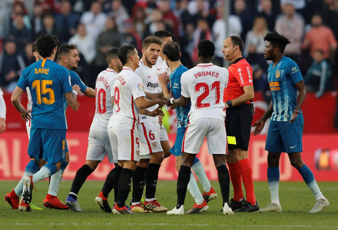 Referee Antonio Mateu Lahoz drops the yellow card as Sevilla's Quincy Promes holds back Atletico Madrid's Juanfran from Sevilla's Daniel Carrico
