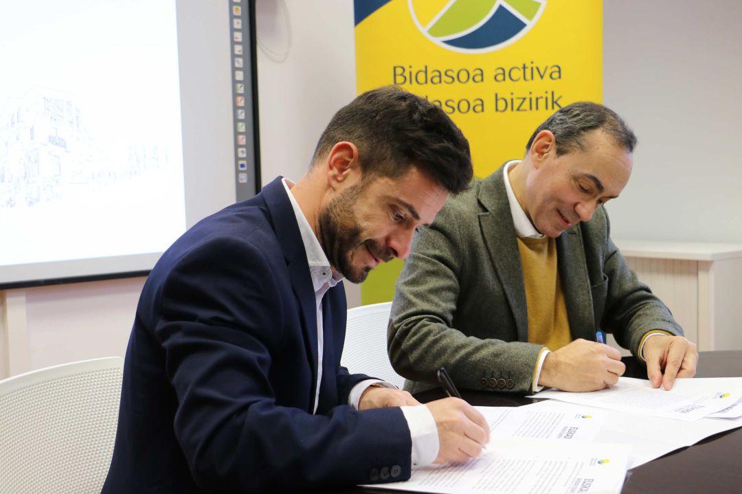 Harkaitz Millán, director general de Basquetour y Miguel Ángel Páez, presidente de Bidasoa Activa, firma el acuerdo de colaboración.