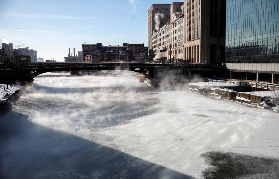 Varias personas cruzan un puente mientras la niebla se eleva desde el río Chicago, este jueves en Chicago