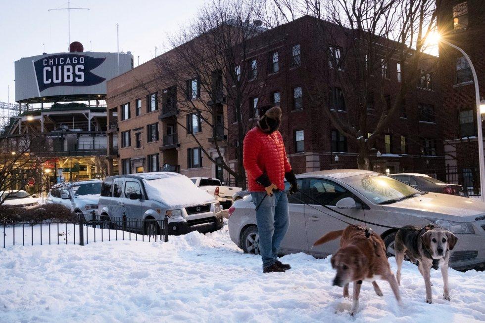 Un hombre pasea con sus perros por calles hasta arriba de nieve