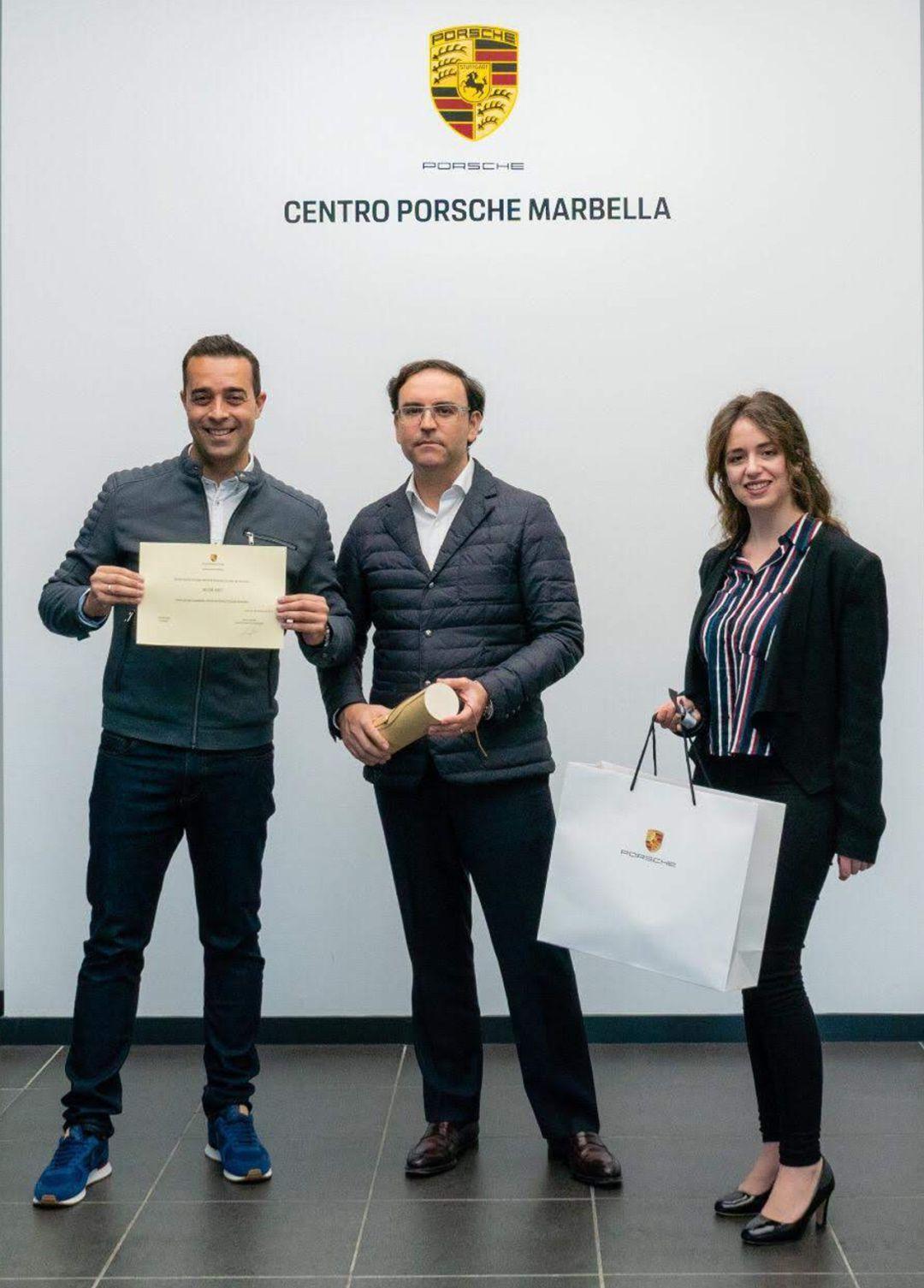 Entrega de la acreditación como Embajador del Centro Porsche Marbella por parte de Rafael Rivero, Gerente de Centro Porsche Marbella y Rocío Laure, Responsable de Marketing