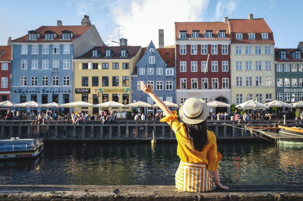 Este informe mundial sobre Felicidad tiene en cuenta variables como la riqueza de un país, las ayudas sociales, la esperanza de vida, la libertad, la corrupción y la calidad de vida de los inmigrantes. En la foto, una joven se relaja en el canal del Nyhavn de Copenague (Dinamarca).