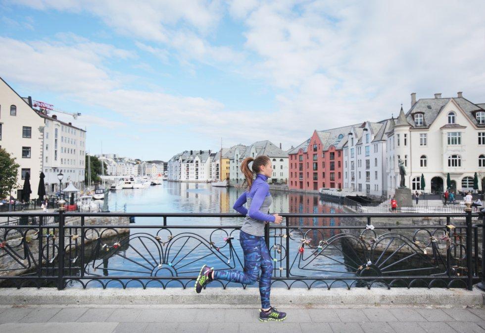 Entre otras variables, el informe mide la felicidad de los residentes en esos países. Pero no solo de los residentes nativos, sino también de sus inmigrantes. En la imagen, una mujer practica deporte por un puente de la localidad noruega de Alesund.
