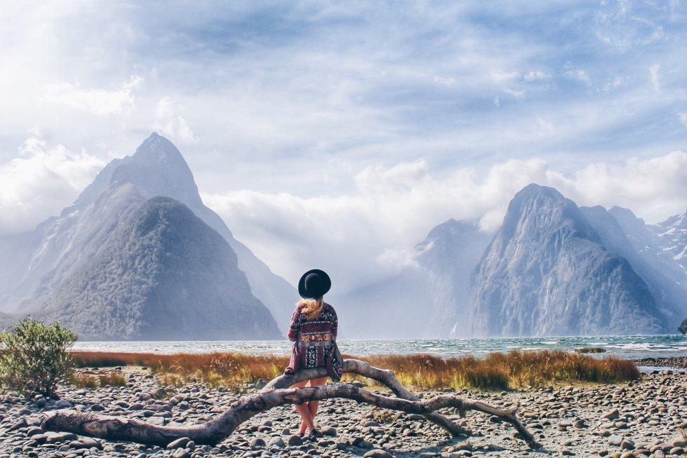 Una joven descansa ante las montañas nevadas de Queestown (Nueva Zelanda).