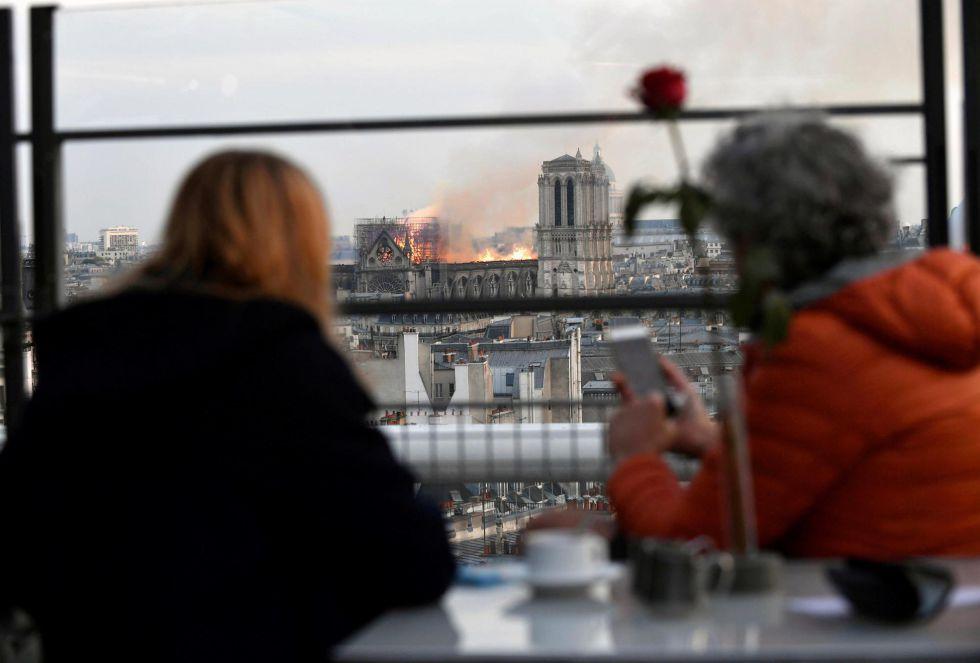 Personas observan un incendio en la catedral de Notre Dame este lunes en París, Francia.
