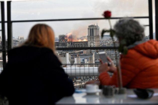 Personas observan un incendio en la catedral de Notre Dame este lunes en París, Francia