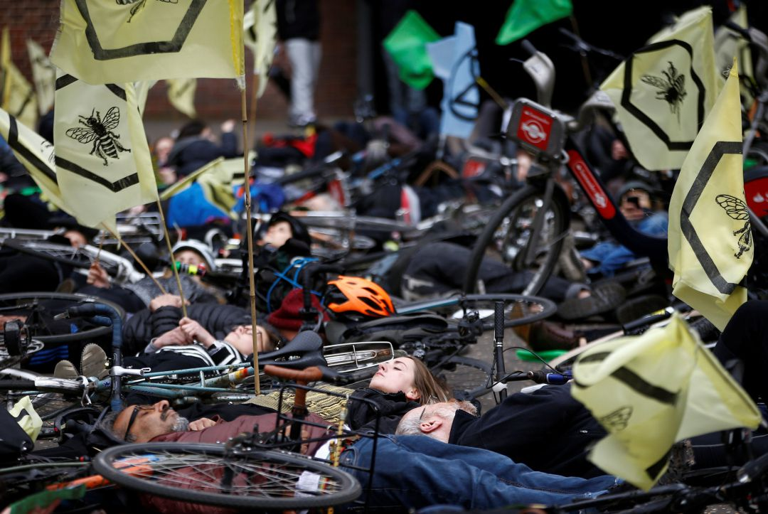 Cyclists lay down as they take part in the Extinction Rebellion protest at the Tate Modern in London,