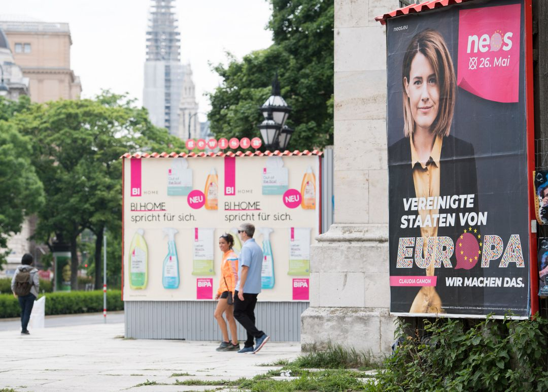 "VIENNA, AUSTRIA - MAY 19: People walk past election campaign posters of the NEOS party during the ""One Europe For All"" march on May 19, 2019 in Vienna, Austria. Thousands of people are marching in similar events in cities across Europe today to voice their opposition against right-wing nationalism and populism ahead of European parliamentary elections scheduled for May 23-26."