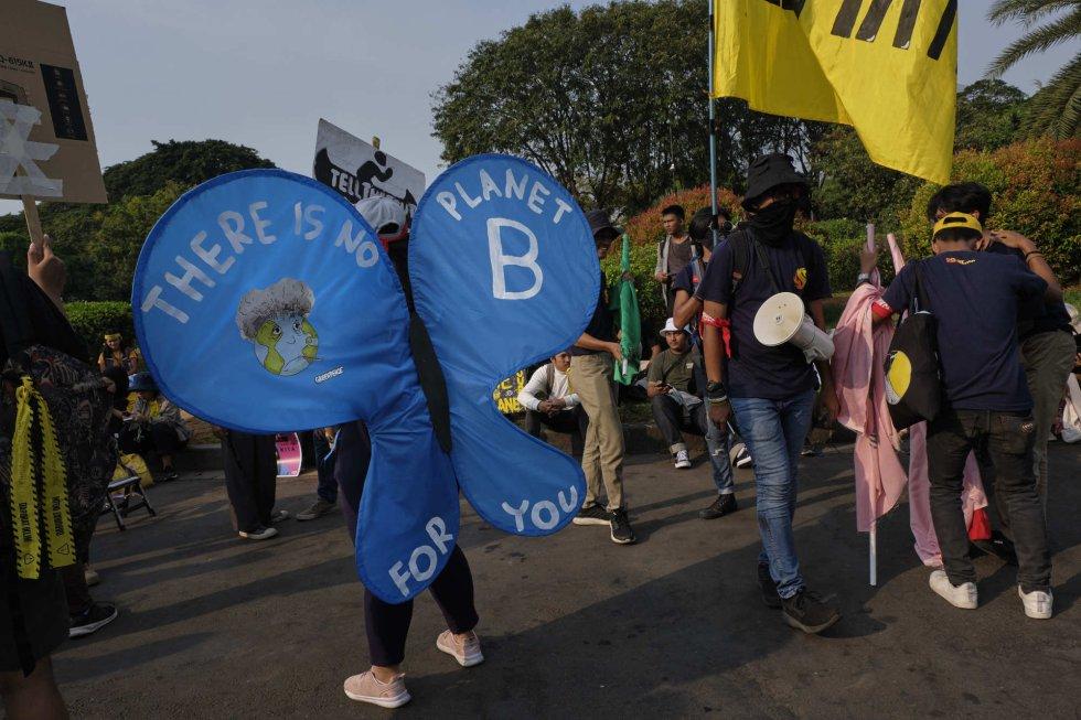 """Un joven disfrazado de mariposa en Jakarta, Indonesia, con el lema """"no hay un planeta B"""", popularizado por la el movimiento global contra el cambio climático."""