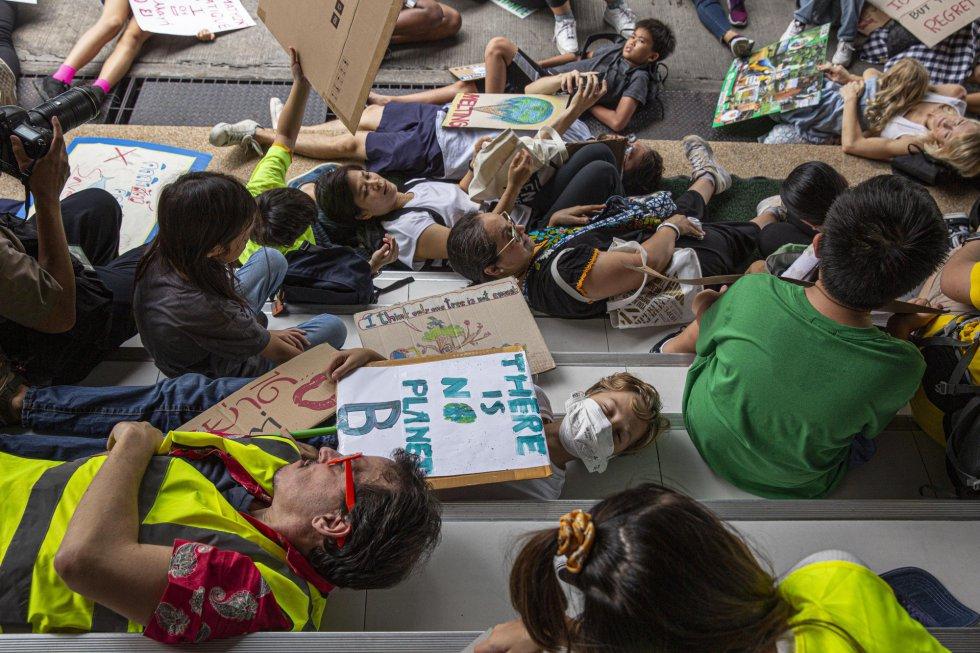 En Bangkok, Tailandia, jóvenes y mayores se echan al suelo para denunciar la necesidad de tomar medidas urgenes para frenar el cambio climático.