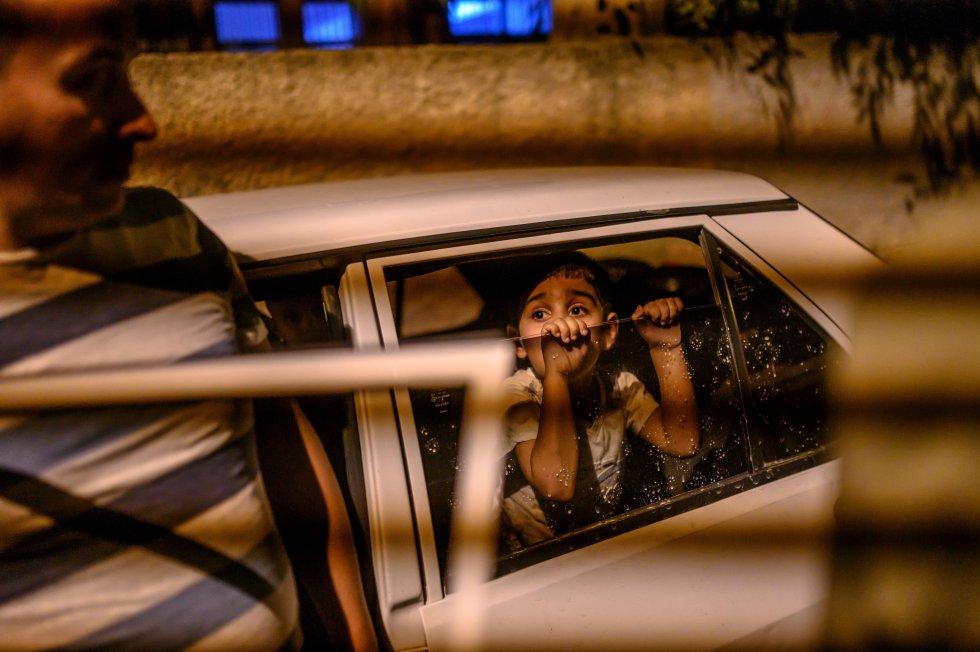 Un niño mira asustado desde el coche listo para dejar su casa en Akcakale una vez han comenzado los ataque de mortero turcos.