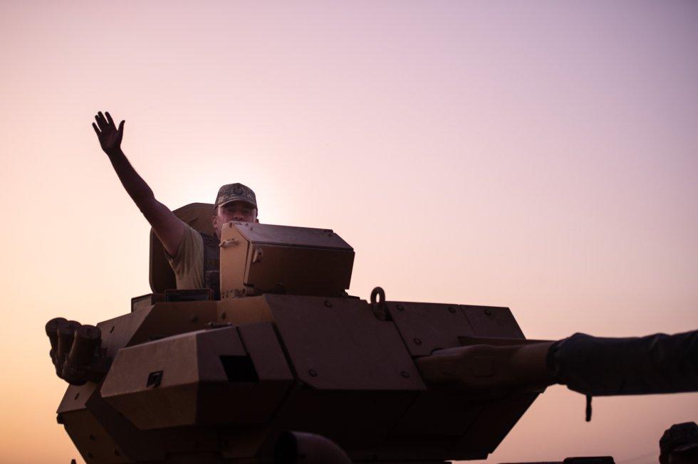 Un soldado turco saluda desde lo alto de un tanque en la frontera con Siria.