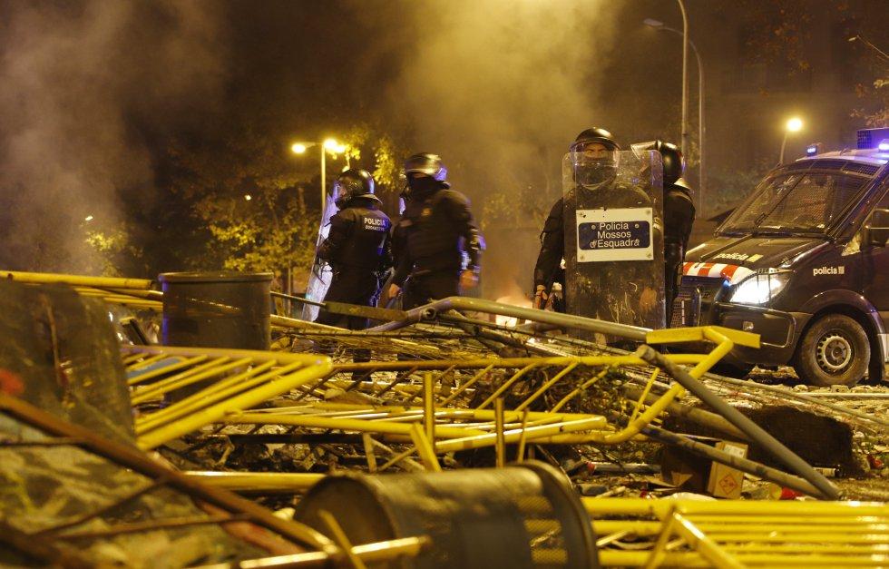 Los Mossos d'Esquadra tras varias valla amontonadas durante las protestas en Cataluña