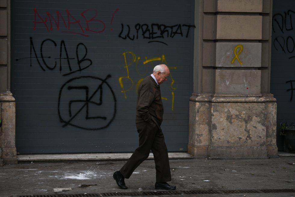 Un hombre camino delante de varias pintadas en la pared