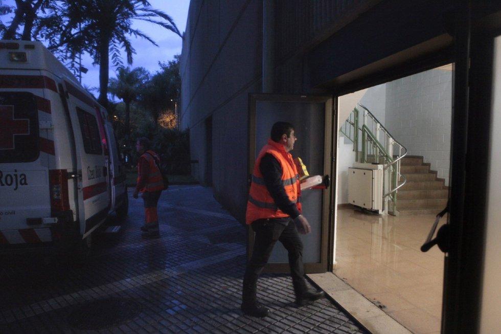 Un miembro de la Cruz Roja lleva comida al Pabellón deportivo de Cambrils donde cincuenta se alojan los niños de entre 6 y 7 años de Sant Just Desvern y sus monitores que fueron desalojados anoche en autobús de la Casa de Colonias La Marinada, a consecuencia de las fuertes lluvias que afectan a Cataluña