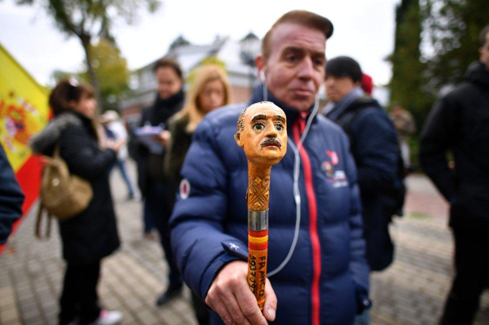 Un simpatizante muestra un bastón con la cara de Franco