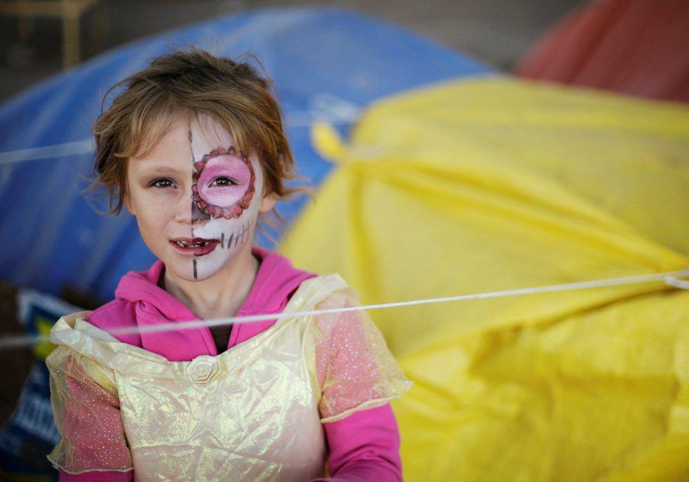 Una niña mexicana, que junto con sus padres huyen de la violencia en su ciudad natal y actualmente están acampando cerca del puente que cruza la frontera internacional Cordova-Americas mientras esperan para solicitar asilo a los Estados Unidos, celebra de Halloween, en Ciudad Juárez.
