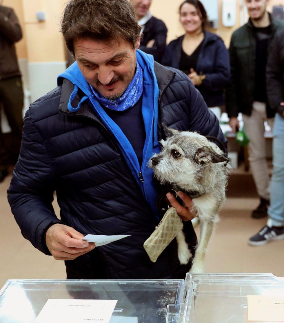 Un elector acompañado de su mascota deposita su voto en la urna