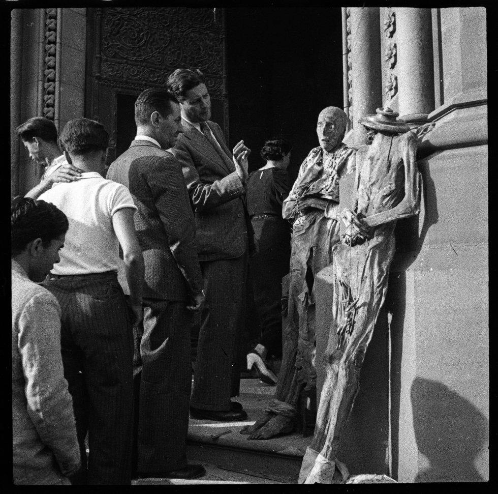 Dos ciudadanos observan en detalle las momias de las monjas expuestas de la iglesia y convento de las Salesas del paseo de Sant Joan de Barcelona. Julio de 1936.