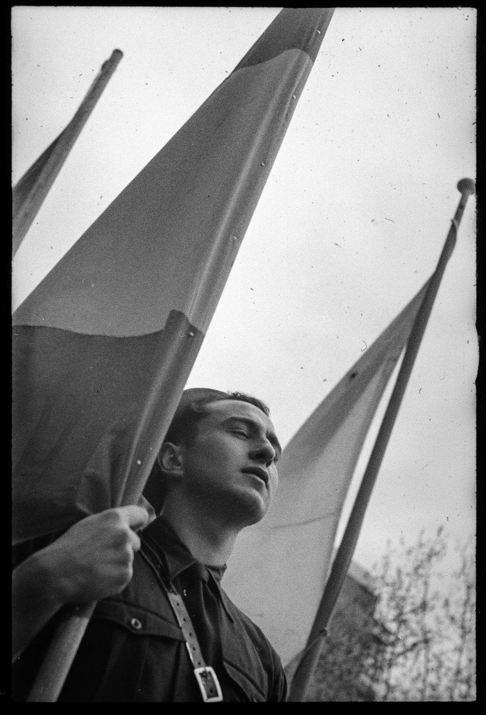 Un joven falangista sostiene una bandera española en el Festival de FET-JONS en homenaje al ministro de Exteriores italiano, Galeazzo Ciano, Barcelona, 11 de julio de 1939