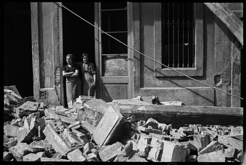 Dos mujeres en medio de los escombros en el Poble Sec de Barcelona después de un bombardeo. 14 de marzo de 1937