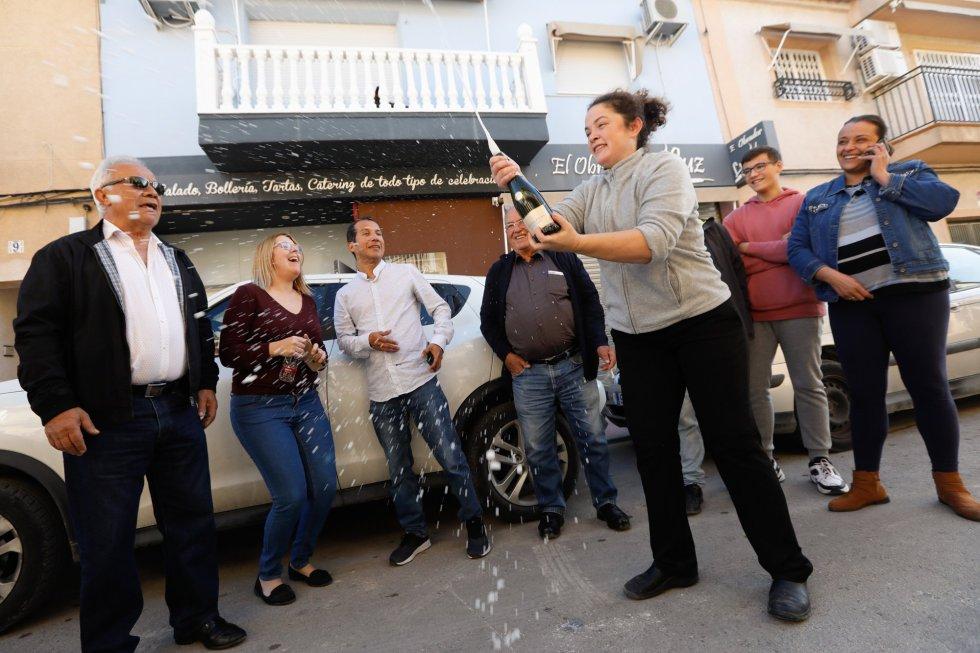 La dueña de Obrador de Luz, Luz María Laveda, descorcha una botella de cava junto con más agraciados con el 'Gordo' de Navidad en Las Torres de Cotillas (Región de Murcia)