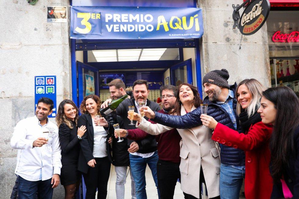 Agraciados por el Tercer Premio del Sorteo Extraordinario de Lotería de Navidad 2019 brindan con champán en la administración situada en la calle Arenal, 16 de Madrid, que ha repartido parte del número 00750