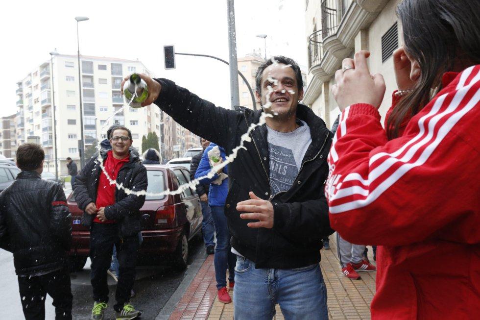 Un hombre celebra con una botella de champán que le ha tocado el Gordo de la Lotería con el nº 26590, frente al gimnasio Seiza 2 donde se repartió el número, en Salamanca