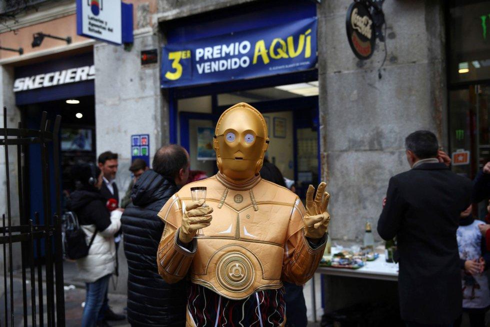 Una persona disfrazada del robot de la Guerra de las Galaxias C-3PO celebra en la administración de lotería 150 en la calle Arenal de Madrid donde se ha vendido una serie del tercer premio