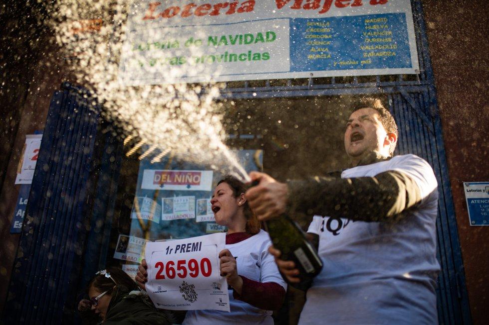 Dos loteros celebran que el décimo premiado con el primer premio de la Lotería de Navidad, el Gordo de la Lotería, el 26590, ha sido vendido en su establecimiento, en Barcelona