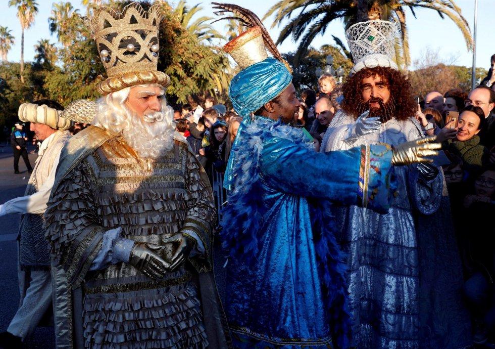 Los tres Reyes Magos saludan a los niños que les esperaban esta tarde a su llegada a Barcelona.